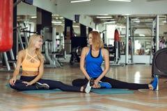 Zwei junge schlanke blonde Frauen, die Übungen in der Turnhalle tun Stockbild