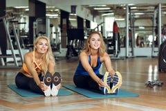 Zwei junge schlanke blonde Frauen, die Übungen in der Turnhalle tun Lizenzfreie Stockbilder