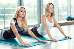 Zwei junge schlanke blonde Frauen, die Übungen in der Turnhalle tun Lizenzfreie Stockfotos