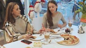 Zwei junge Schulmädchenfreunde, die Pizza essen und in einem Caféspaß sprechen In der Hintergrundansicht einer Stadtstraße Herbst stock video