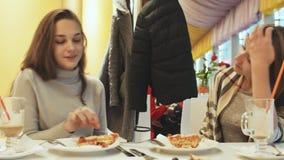Zwei junge Schulmädchenfreunde, die Pizza essen und in einem Caféspaß sprechen Herbst, Winter stock footage