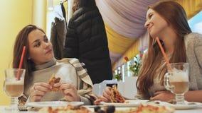 Zwei junge Schulmädchenfreunde, die Pizza essen und in einem Caféspaß sprechen Herbst, Winter stock video