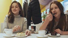 Zwei junge Schulmädchenfreundinnen in einem trinkenden Kaffee des Cafés und im essen Gebäck Herbst, Winter stock video
