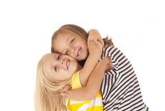 zwei junge Schwestern, die eine liebenswerte Umarmung geben  Lizenzfreies Stockfoto