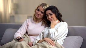 Zwei junge Seifenoper zu Hause aufpassende und schreiende Freundinnen, gl?ckliches Ende lizenzfreies stockfoto
