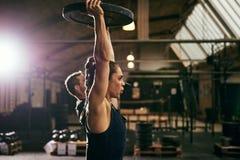 Zwei junge sportive Athleten, die mit Gewichten trainieren Stockfotografie