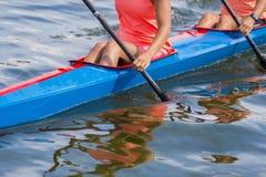Zwei junge Sportlerinnen auf dem Rudern des Kajaks auf See während des Wettbewerbs stockfoto