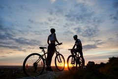Zwei junge Sportleute auf Mountainbiken stehen auf Felsen an der Spitze des Hügels, der nach Sonnenuntergang sucht stockfotos