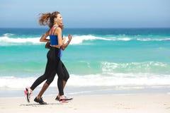 Zwei junge sportliche Frauen, die auf dem Strand laufen Stockfotografie