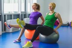 Zwei junge sportliche Frauen, die gymnastische Übungen tun oder in der Eignungsklasse trainieren Lizenzfreies Stockfoto