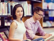 Zwei junge Studenten an der Bibliothek Lizenzfreies Stockfoto