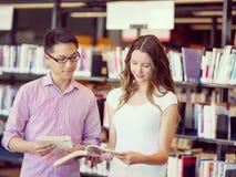 Zwei junge Studenten an der Bibliothek Lizenzfreie Stockfotografie