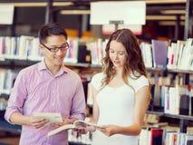 Zwei junge Studenten an der Bibliothek Stockfotografie