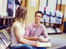 Zwei junge Studenten an der Bibliothek Lizenzfreies Stockbild