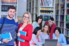 Zwei junge Studenten, die an der Bibliothek zusammenarbeiten Stockbild