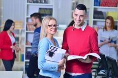 Zwei junge Studenten, die an der Bibliothek zusammenarbeiten Stockfotografie