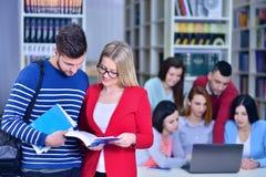 Zwei junge Studenten, die an der Bibliothek zusammenarbeiten Lizenzfreies Stockfoto