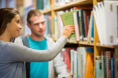 Zwei junge Studenten, die ein Buch in der Bibliothek vorwählen Stockbild