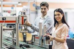 Zwei junge Studenten, die zusammen an einem Projekt im Labor arbeiten Stockfoto
