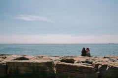 Zwei junge türkische Mädchen in den hijabs sitzen auf dem Damm das Meer sprechend und bewundernd Istanbul, die Türkei lizenzfreies stockfoto