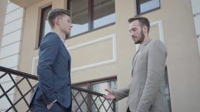 Zwei junge Teilhaber, die Hände auf der Terrasse rütteln Die Männer machten gerade gutes Abkommen Gesch?ftliche Beziehungen unter stock video