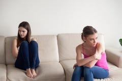 Zwei junge verärgerte Frauen, die auseinander auf Sofa sitzen lizenzfreies stockfoto