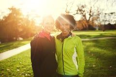 Zwei junge weibliche umarmende Athleten bei der Stellung im Park stockfotos
