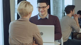 Zwei junge Wirtschaftler, die Laptop in der Lobby des modernen Büros verwenden stock video