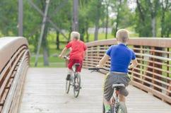 Zwei Jungen, die auf Brücke zu North Dakota radfahren Lizenzfreie Stockfotografie