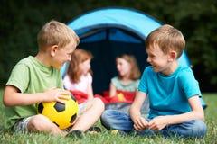 Zwei Jungen, die auf Camping-Ausflug sprechen lizenzfreies stockfoto
