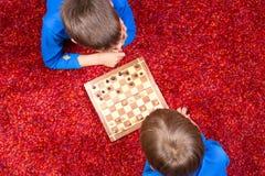 Zwei Jungen, die auf dem Boden liegen und Schach spielen lizenzfreie stockbilder