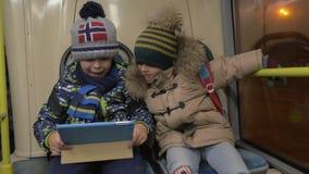 Zwei Jungen, die auf einen Pendlerbus fahren stock footage