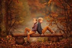 Zwei Jungen, die auf einer Bank im Herbst sitzen, parken Lizenzfreies Stockbild