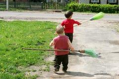 Zwei Jungen, die in der Straße mit Besen spielen stockfoto