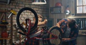 Zwei Jungen, die ein Fahrrad in einer Garage reparieren stock footage