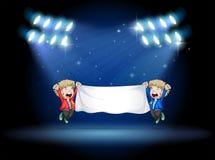 Zwei Jungen, die eine Fahne unter den Scheinwerfern halten Stockfoto