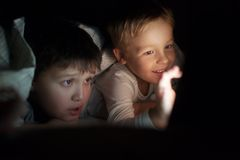 Zwei Jungen, die Film oder Karikatur auf Auflage nachts aufpassen Stockfotografie