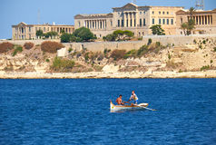 Zwei Jungen, die im Boot auf dem Wasser des großartigen Hafens mit t rudern lizenzfreie stockbilder
