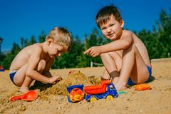 Zwei Jungen, die im Sand auf dem Strand spielen lizenzfreie stockfotos