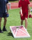 Zwei Jungen, die Maisloch spielen stockbilder