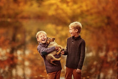 Zwei Jungen, die mit einem Hund spielen stockbild
