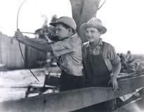 Zwei Jungen, die mit Pfeil und Bogen spielen Stockfotos