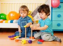 Zwei Jungen, die mit Pyramideblöcken spielen Stockbilder