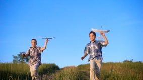 Zwei Jungen, die mit seinen Flugzeugen am Feld laufen stock video