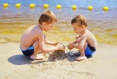 Zwei Jungen, die Sandburg auf dem Strand errichten Stockbild