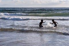 Zwei Jungen in einem Wasser-Kampf in der Brandung vom Mittelmeer stockbild