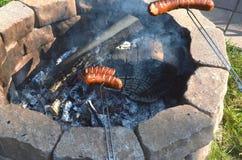 Zwei Jungen grillen, oder grillende Krakauer über einem offenen Feuer bilden in ihrem Hinterhof Löcher stockfotografie