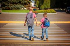 Zwei Jungen mit dem Rucksackgehen, warmen Tag auf der Straße an halten Stockfotografie