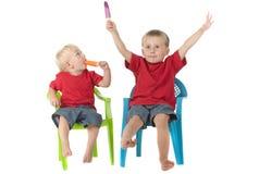 Zwei Jungen mit Popsicles auf Rasenstühlen Stockfotos