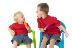 Zwei Jungen mit Popsicles auf Rasenstühlen Stockfotografie